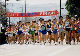 Hundreds of runners, wearing sashes and numbers leaving the starting gate of an ekiden