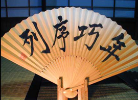 A close-up of a hand fan that contains Japanese writing on it.