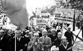 Men in bandana's march and cheer while holding signs