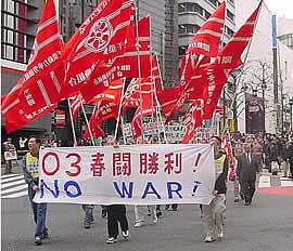 春闘の際に、組合ごとに赤い旗を掲げて行進をしています。 街を歩く春闘のデモ隊。2003年。 写真