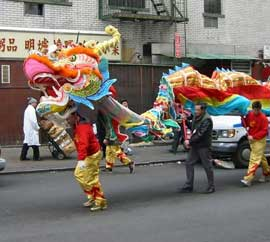 People walking a dragon in a parade.