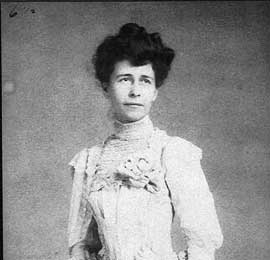 Photo of woman in white lace dress with high neck.